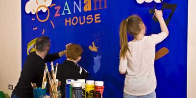 Image of Ozanam Youth Group Two painting mural in their base room